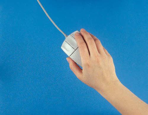 Käsi pitelee tietokoneen hiirtä.