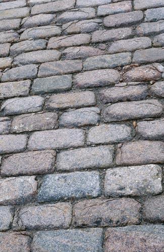 """Katukiviä Tuomiokirkon lähellä (Snellmaninkatu 3). Uudelleen asennettuja kiviä on koetettu """"vanhentaa"""" kuumentamalla niiden pintaa polttolampulla, jolloin kivet ovat pinnaltaan rikkoutuneet. (kuoriutuneet pallomaisesti)."""