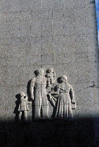 """Kluuvin kauppakeskus, entinen Elannon tavaratalo. Veikko Leistén 1952.Rakennus on päällystetty Uudenkaupungin harmaalla tonaliitilla. Rakennuksen kulmassa (päädyssä) on Aimo Tukiaisen samaan kiveen veistämä reliefi """"Perhe"""". Aleksanterinkatu 9 - Kluuvikatu 5."""
