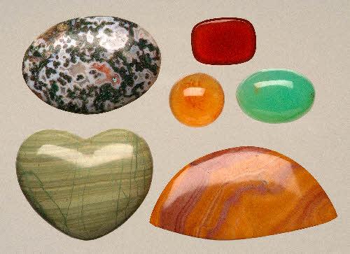 Erilaisia kalsedonimuunnoksia. Ylhäällä vasemmalla sammalakaatti (pituus 35 mm), alimmaiset akaattia. ylhäällä oikealla punainen sardi, keltainen karneoli, vihreä krysopraasi, Tansania. (Seppo Lahden kokoelmat) Näytteiden värit aiheutuvat mineraalien sisältämistä pigmenttihiukkasista.