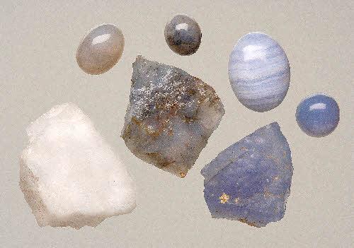 Erivärisiä kvartseja. Vas. alh. lumikvartsia, ylh. keskellä hiottu ja keskellä raakakivi sinikvartsia, Lapua, Simpsiönvuori. Klo kymmenessä sama kivi Espoosta. Oikealla olevat sinertävät mineraalit sinistä kalsedonia Perusta. Raidallista kiveä voi kutsua myös akaatiksi. (andean blue).