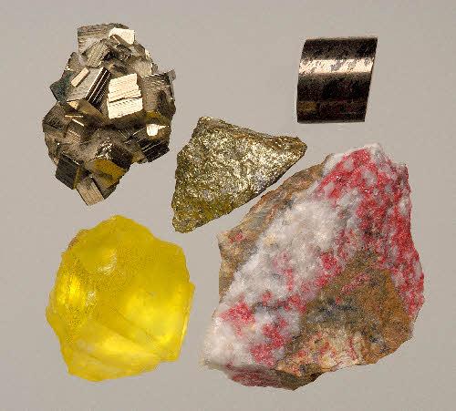 Ylhäällä sulfidimineraaleja: rikkikiisu, kuparikiisu ja magneettikiisu. Vasemmalla alhaalla keltaista rikkiä ja oikealla alhaalla punaista auripigmenttiä.
